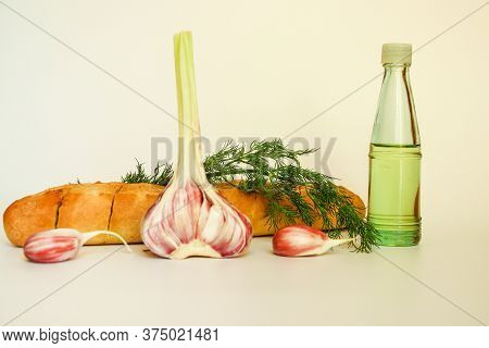 Fresh Crispy Baguette With Garlic Oil And Herbs. A Delicious Still Life Of Baguette, Young Garlic, F