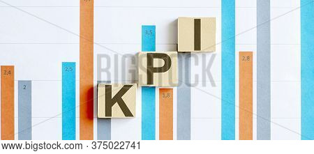 Kpi Word Letters On Wooden Blocks On Chart Background. Business Concept.