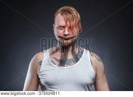 Photo Of A Tattooed Scary Mad With Horror Make-up
