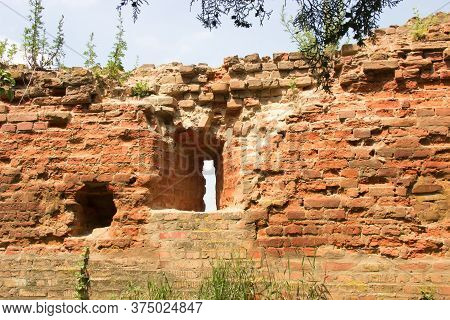 Fragment Of Partially Damaged Defense Brick Wall With Embrasure Of Mediaeval Fortress, Overgrown Wit