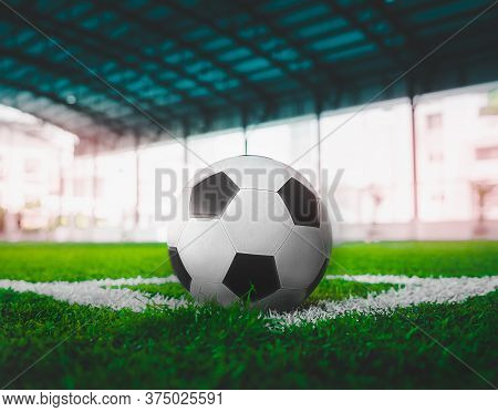 Used Classic Black And White Soccer Ball On Football Corner Marking Field With No People.