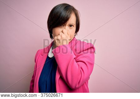 Young down syndrome business woman over pink background smelling something stinky and disgusting, intolerable smell, holding breath with fingers on nose. Bad smell