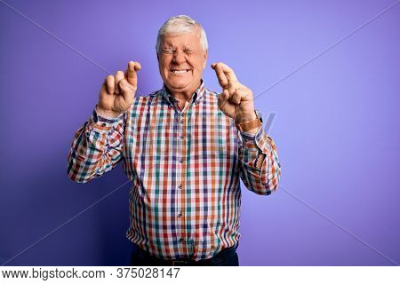 Senior handsome hoary man wearing casual colorful shirt over isolated purple background gesturing finger crossed smiling with hope and eyes closed. Luck and superstitious concept.