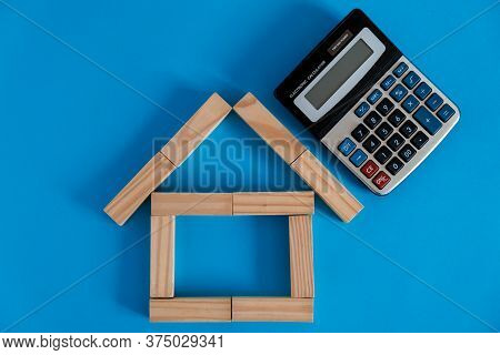 Closeup Of House Wooden Model And Keys With Calculator On Blue Background. Mortgage Property Insuran