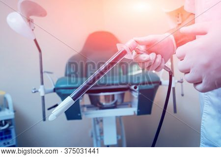 Proctologist Holding An Anoscope Against A Proctological Chair.