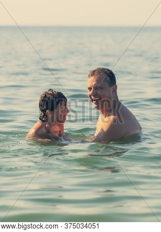 Father Teaching His Son How To Swim. Father And Son Spending Time Together Swimming In The Sea. Vaca