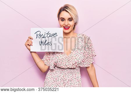 Young beautiful blonde woman holding positive vibes banner looking positive and happy standing and smiling with a confident smile showing teeth