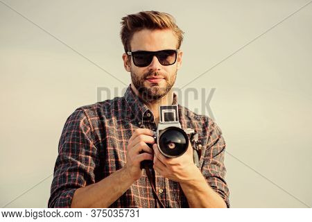 Blogger Shooting Vlog. Handsome Blogger Guy Traveler Retro Camera. Manual Settings. Photojournalist