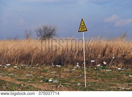 Yellow Triangle With Skull And Crossbones Symbol On Abandoned Territory With Trash. Garbage Waste Fi
