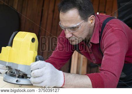 Craftsman Carpenter Works On Wooden Workpiece With Milling Tool Close Up At Cottage Workshop. Proces