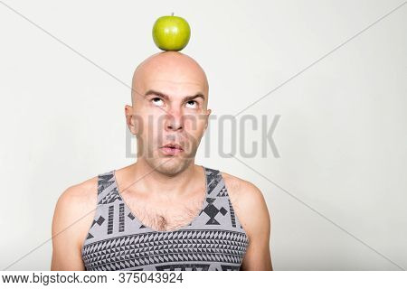 Portrait Of Bald Man With Apple On Top Of Head