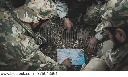 Military Officers Studying The Plan On The Map