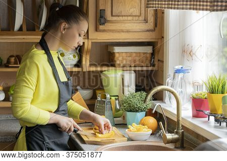 Female Cook Slices Sweet Pepper On Wooden Board, Rustic Traditional Kitchen On Background, Woman Coo