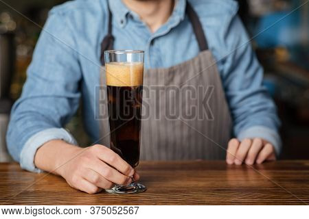 Dark Ale With Foam. Barman In Apron Holds High Glass Of Beer On Wooden Bar Counter, Close Up, Croppe