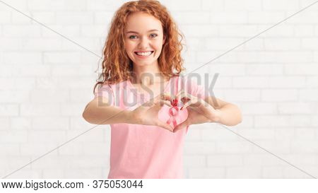 Breast Cancer Cure. Girl Gesturing Heart Shape Framing Pink Ribbon Cancer Symbol On T-shirt Over Whi