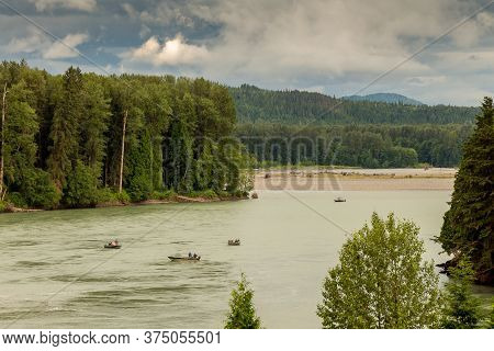Fishermen Fishing For Salmon On The Skeena River Below Terrace, During A Cloudy Day In Summer, In Br