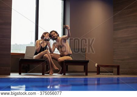 Couple In Love Enjoying Their Vacation, Relaxing By The Spa Center Swimming Pool, Sitting On Sunbed,