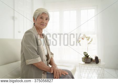 Smiling Senior Woman Sitting On Sofa And Looking At Camera. Awaken Old Woman With Grey Hair And Paja