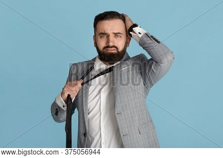 Businessman In Formalwear Holding His Head And Tie In Despair Against Blue Background