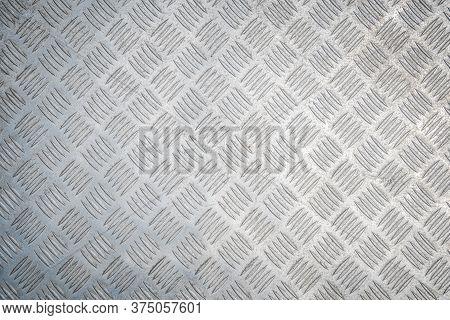 Industrial Background. Metal Diamond Plate Known As Chakkered Or Tread Plate. Metallic Pattern.