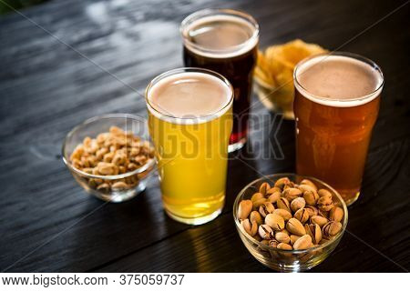 Glasses With Three Different Types Of Beer. Nuts, Rusks And Chips In Bowls On Dark Wooden Table, Clo
