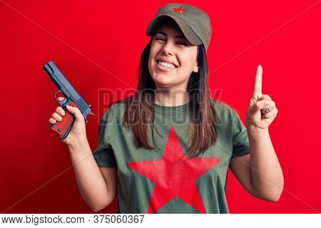 Young beautiful brunette woman wearing t-shirt with red star communist symbol holding gun smiling with an idea or question pointing finger with happy face, number one