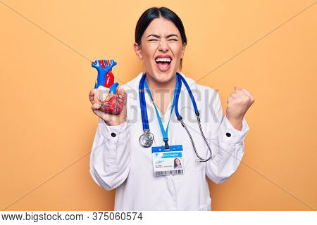 Young beautiful cardiologist woman wearing stethoscope holding heart over yellow background screaming proud, celebrating victory and success very excited with raised arm