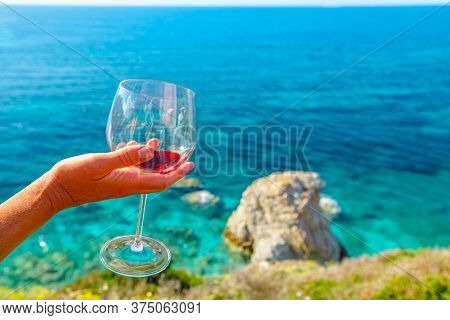Womans Hand Holding Wine Glass Reflecting Limestone Of Famous Sansone Beach From Panoramic Terrace I