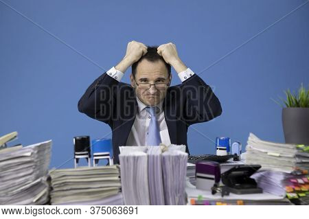Feeling Tired And Overworked Businessman Rips His Hair Stressed Out At Office Desk Loaded Of Paperwo