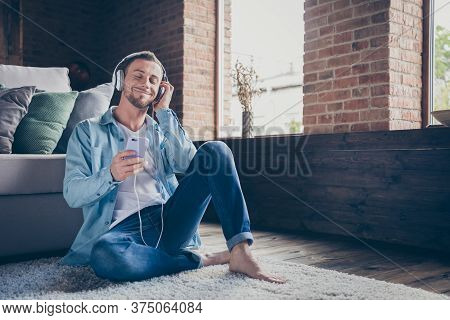 Photo Of Handsome Homey Guy Sit Comfy Carpet Near Couch Browsing Telephone Check Song Playlist Liste