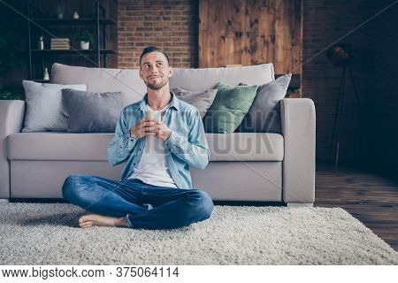 Photo Of Handsome Homey Guy Sitting Comfy Fluffy Carpet Near Couch Drink Hot Fresh Coffee Look Up Dr
