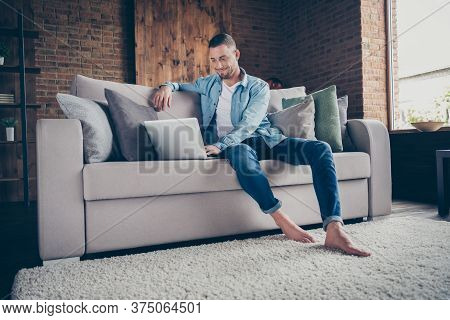 Photo Of Handsome Homey Barefoot Guy Relaxing Sitting Comfy Couch Browsing Notebook Freelancer Remot