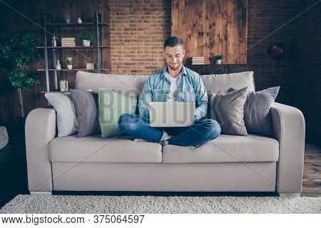 Photo Of Handsome Homey Guy Relaxing Sitting Comfy Couch Legs Crossed Browsing Notebook Freelancer R