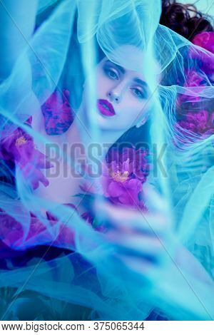Beauty and flowers concept. Portrait of a magnificent brunette woman with bright make-up lying among peony flowers covered with a veil and surrounded by haze. Cosmetics, make-up. Perfumery.