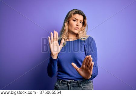 Young beautiful blonde woman wearing casual t-shirt over isolated purple background Moving away hands palms showing refusal and denial with afraid and disgusting expression. Stop and forbidden.