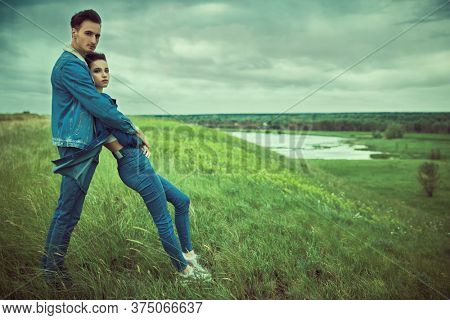Portrait of a young couple in love, embracing in the fresh air in nature against cloudy sky. People in love. Summertime.