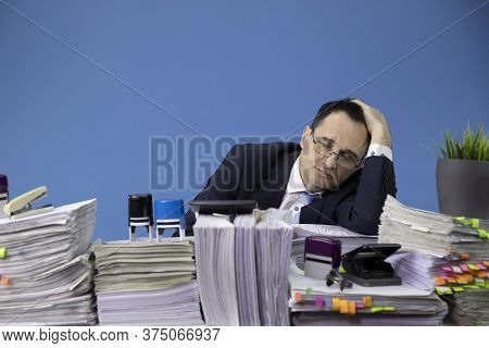 Overwhelmed Overworked Businessman Asleep At Office Desk Loaded Of Paperwork, Lot Of Papers And Docu