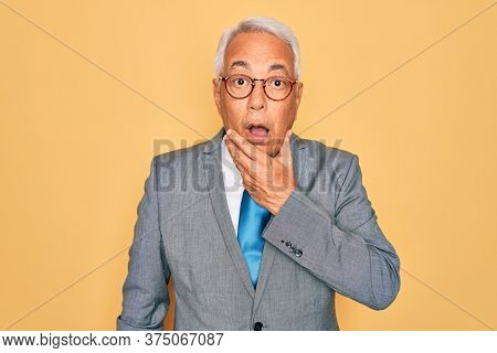 Middle age senior grey-haired handsome business man wearing glasses over yellow background Looking fascinated with disbelief, surprise and amazed expression with hands on chin