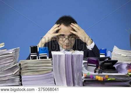 Confused Accountant Looking At Camera Surrounded By Huge Piles Of Documents. Fatigue And Overload Co