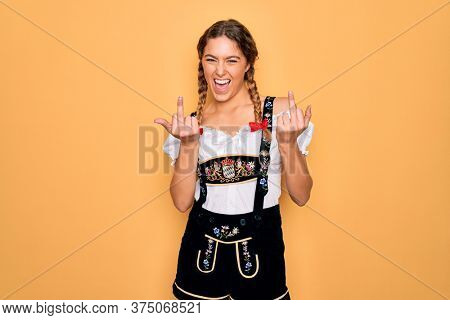Young beautiful blonde german woman with blue eyes wearing traditional octoberfest dress Showing middle finger doing fuck you bad expression, provocation and rude attitude. Screaming excited