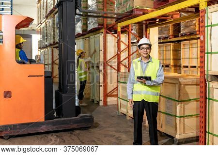 Portrait of warehouse manager hold digital tablet with warehouse worker operate forklift to check inventory in background. Reopening business warehouse technology and logistic concept.