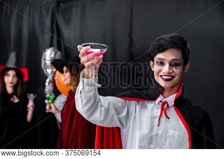 Portrait of asian young adult teenage man wear Halloween costume cloth with group of friends in Halloween party background. Halloween celebrate and international holiday concept.