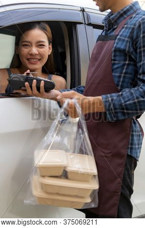 Woman customer make mobile payment contactless technology on drive thru food service restaurant while picking up. Drive through is new normal more popular after coronavirus covid-19 pandemic.