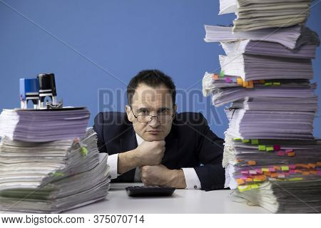 Tired Office Worker Puts His Head On His Fists, Surrounded By High Stacks Of Documents. Fatigue And