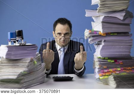 Tired Office Worker Make Fuck Sign Tired Sitting At Desk With Huge Pile Of Documents. Fatigue And Ov