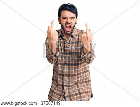 Young hispanic man wearing casual clothes showing middle finger doing  bad expression, provocation and rude attitude. screaming excited