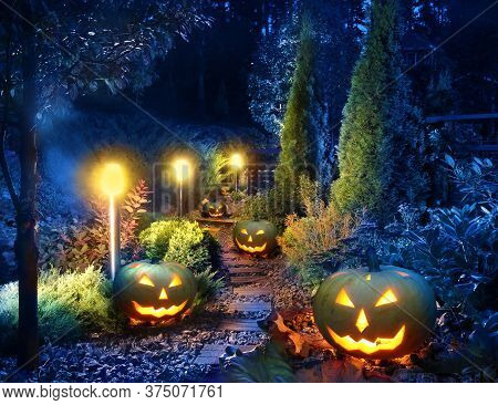 Dark Home Garden Illuminated Patio Lights With Halloween Pumpkin Lanterns Along The Path