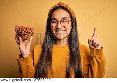 Young beautiful asian woman holding bowl with german baked pretzels over yellow background surprised with an idea or question pointing finger with happy face, number one