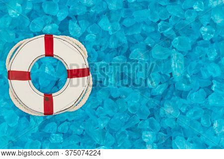 Whitewash Life Preserver On Teal Textured Beach Glass Background With Copy Space For Beach Or Holida