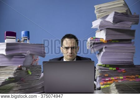 Businessman In Glass And Tie Sitting At Office Desk With Huge Pile Of Documents Working On Computer